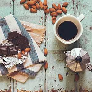 dark chocolate, almonds, and fresh coffee on a table